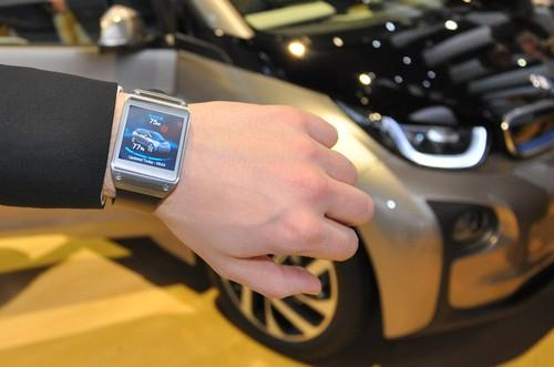 A BMW official shows off the all-electric i3 linked to a Samsung Galaxy Gear smartwatch at CES 2014. The watch can command the i3 to sound its horn and display info such as charge remaining in the battery.