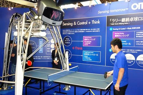 Omron's table tennis-playing robot takes on a human opponent. The machine uses computer vision and predictive algorithms to sustain rallies, but sometimes misses when spin is put on the ball.