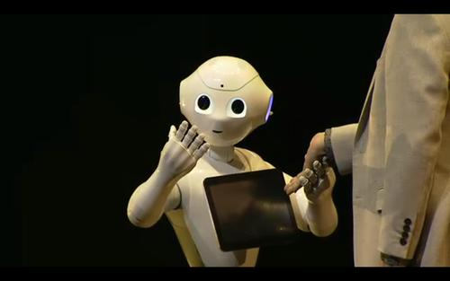 Pepper, a new humanoid robot for household use, holds hands with SoftBank CEO Masayoshi Son at a press event outside Tokyo on Thursday.