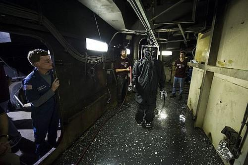 The U.S. Navy's Shipboard Autonomous Firefighting Robot (SAFFiR) undergoes testing in rain gear aboard a decommissioned Navy vessel. It can manipulate doors and fire hoses and could work with drones and human firefighters in the future.