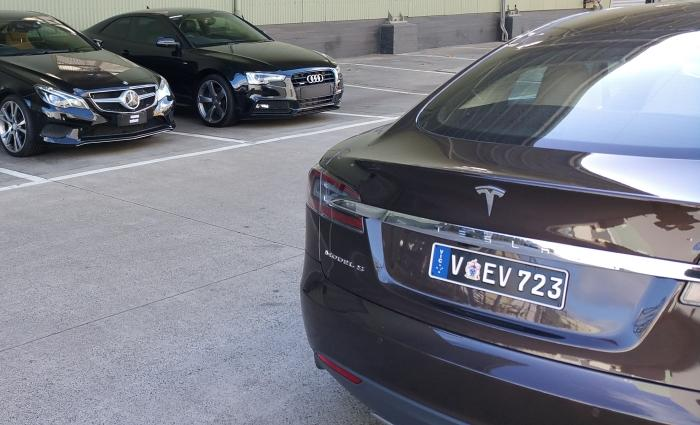 Tim Washington's Brown Model S in the foreground, set against a backdrop of European rivals; licence plate VEV723
